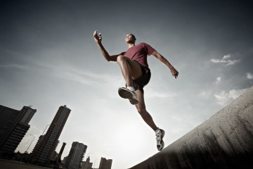 hispanic man running and jumping from a wall